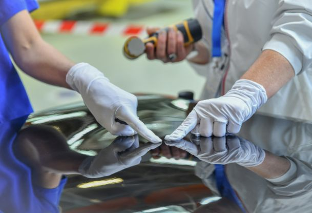 Technicians Examining Scratch on Black Car